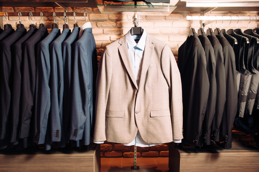 Many men's business suits of different colors. Modern boutique with clothes for business people. Horizontal photo
